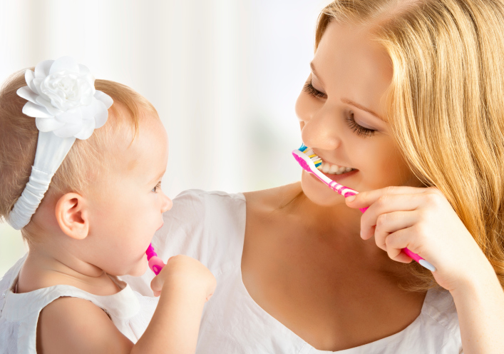 Mom brushes teeth with daughter